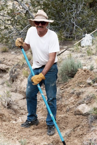 Oscar Simpson from Back Country Horseman and former Executive Director of the New Mexico Wildlife Federation rakes in some native seed.